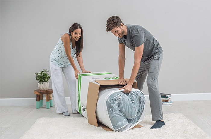 couple unwrapping Ghostbed bed in a box