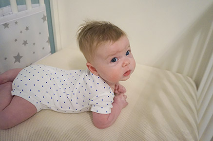 Hazel enjoying the infant phase of Naturepedic crib mattress