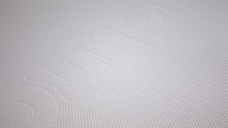 Purple mattress logo on bed