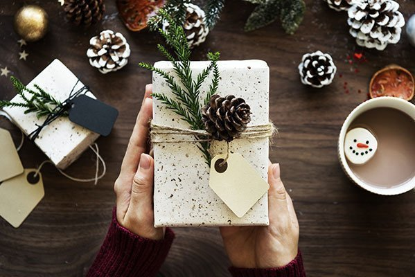 Top gift ideas this holiday - person holding Christmas present