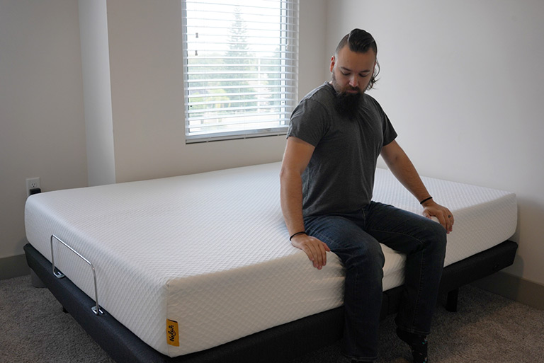 Man demonstrates edge support on the Nolah mattress
