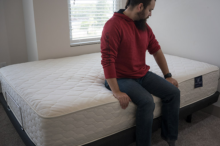 Man demonstrates edge support on the WinkBed's EcoCloud Mattress