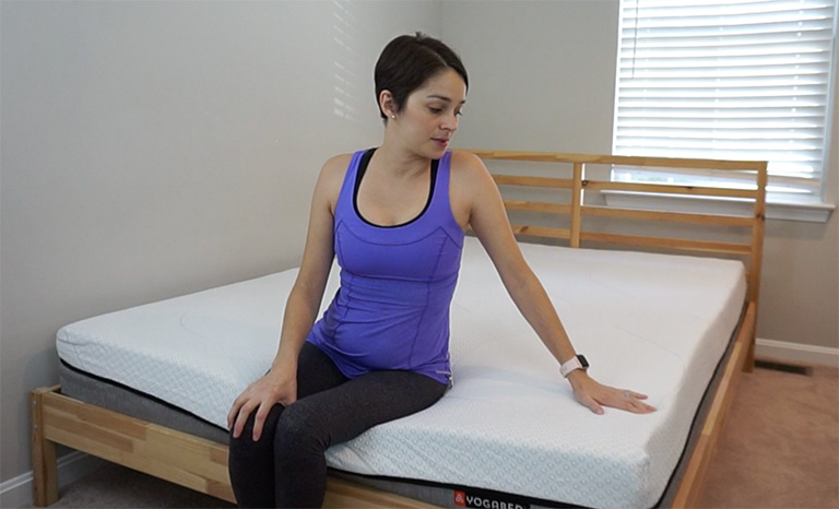 Woman testing Edge Support in the Yogabed Mattress Review