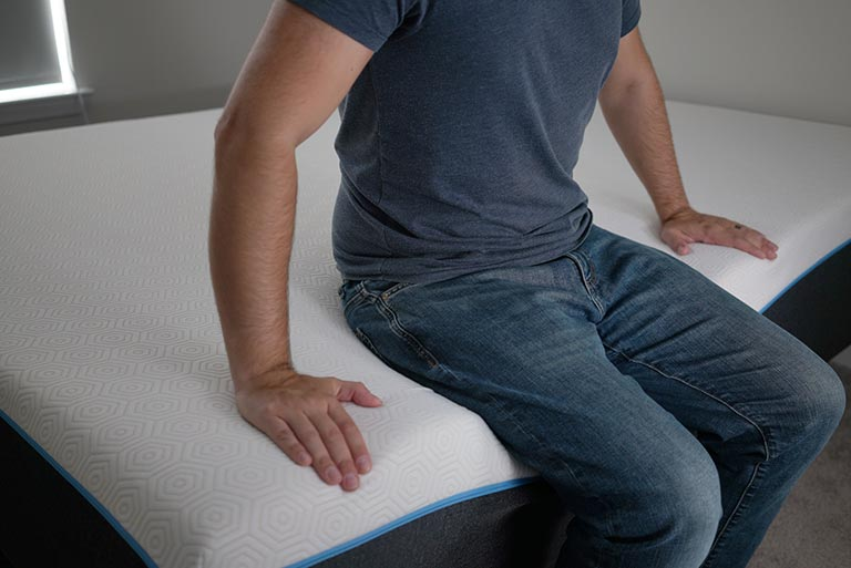 Man sitting on edge of bed to demonstrate edge support