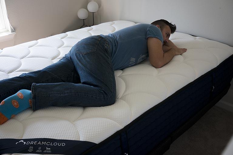Man demonstrates combination sleeping on the DreamCloud mattress