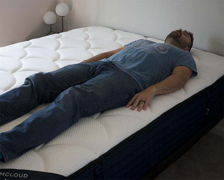 Man demonstrates back sleeping on the DreamCloud mattress
