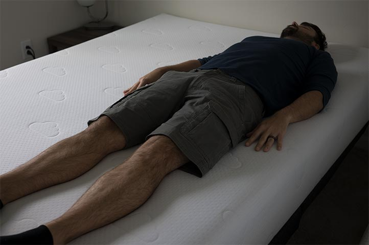 Man demonstrates back sleeping on the Puffy mattress