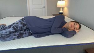 Woman demonstrates side sleeping on Nectar mattress