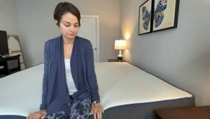 Woman sits on edge of Nectar bed to demonstrate edge support